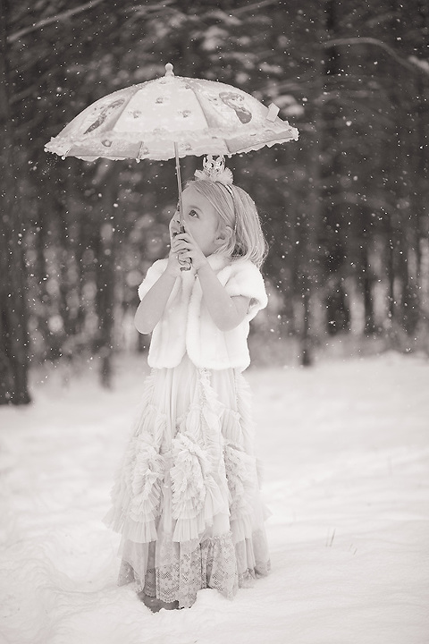 Little girl with Dollcake dress on in the snow with a parasol