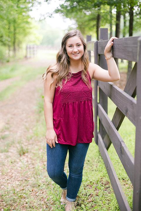 senior girl in prom dress in woods